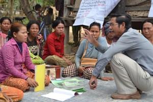 Projektkoordinator Pich Sophin, ADDA, forklarer selvhjælpsgruppe om kassebøgerne.